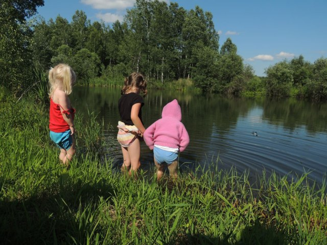 three girls wading in the pond